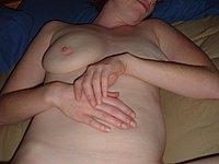 Junge willige Hausfrau nackt auf dem Bett