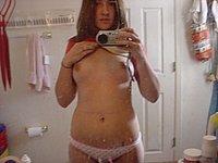 Mädchen mit kleinen Brüste fotografiert sich selbst nackt im Badezimmer